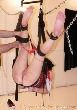 Julie, hogtied on a swing, gets stripped naked after getting caned